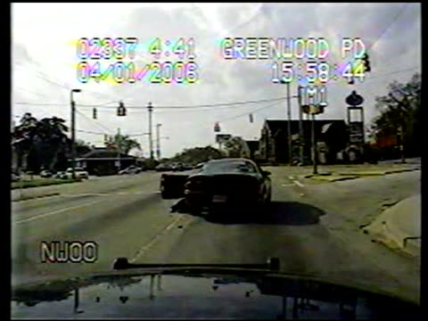 / 2 dashcam angles of police shootout with suspect / car racing through neighborhoods / suspect's car stops at traffic light driver door opens and... - 追いかける点の映像素材/bロール