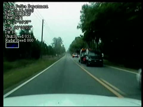 / dashcam footage of tow truck pulling an suv that is chased by several police cars / an officer on foot runs out of the way as the suspect drives at... - 追いかける点の映像素材/bロール