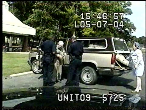 vidéos et rushes de / dashcam video of officers talking with woman and man accused of reckless driving / eldersly man shuffles back to his car grabs his four pronged... - frapper activité physique