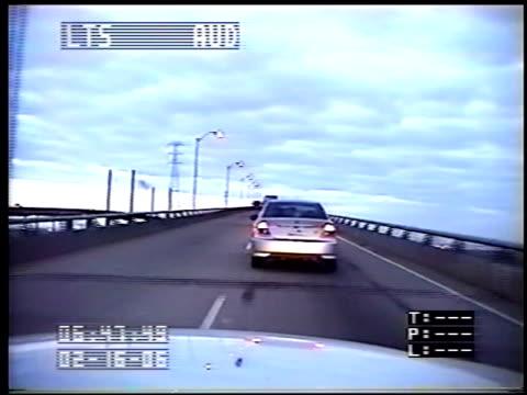 vídeos de stock, filmes e b-roll de / dashcam video of police car following suicidal woman in car on road toward bridge / woman stops car on bridge and tries to get out as police... - a parar