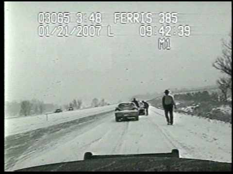/ dashcam video of police officer standing on side of road next to car when suddenly another car comes sliding sideways through the snow and crashes... - 衝突事故点の映像素材/bロール