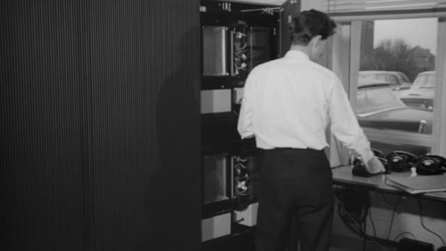 1969 ms data bank technician working with computer storage system / united kingdom - addierrolle stock-videos und b-roll-filmmaterial