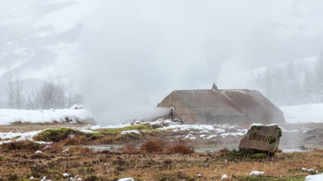 A datime winter time lapse of Smidur, a geyser in the Geysir Geothermal Field (formerly Hverasandar) in Iceland featuring steam rising from both Smidur and a man made structure in the background (on the Golden Circle tour route)