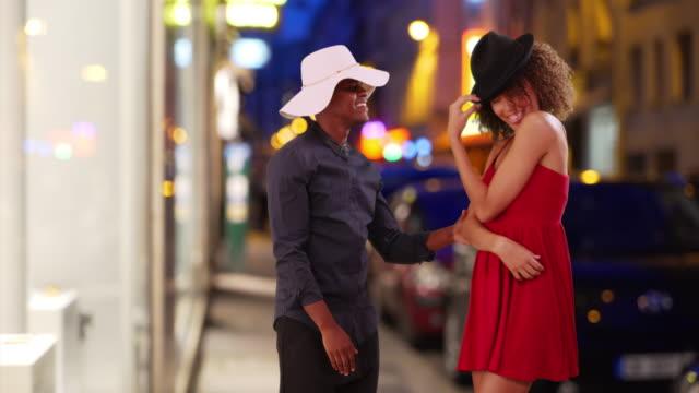 vidéos et rushes de dating couple model each other's hats on city street at night - robe d'été