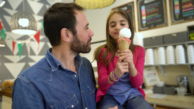 daughter and father enjoying an ice cream at the ice cream parlor and saleswoman passing her the ice cream - serving scoop stock videos & royalty-free footage