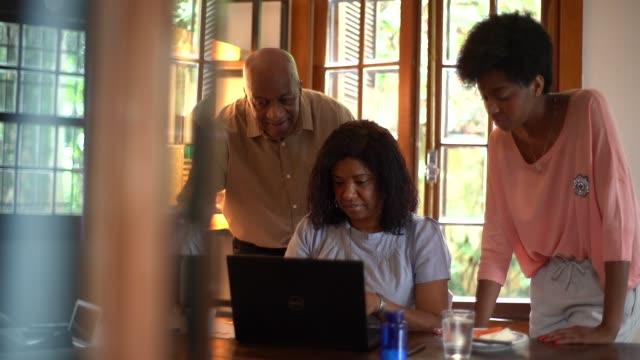 vídeos y material grabado en eventos de stock de hija y padre ayudar a madre mientras usa la computadora - 50 59 años