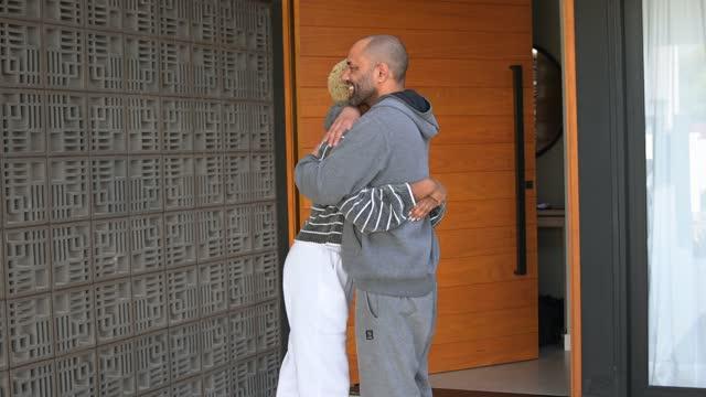娘と父親は自宅のガレージでお互いに抱き合う - dia点の映像素材/bロール
