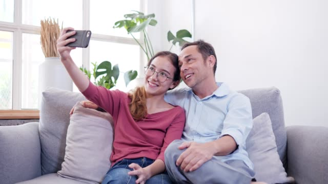daughter and father selfie in living room. - 45 49 years stock videos & royalty-free footage