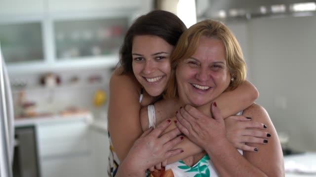 娘と自宅を抱く母親