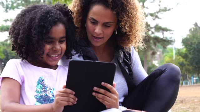 Daughter and Mother Enjoying a Day at Park Using Tablet