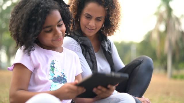 daughter and mother enjoying a day at park using tablet - single parent family stock videos & royalty-free footage