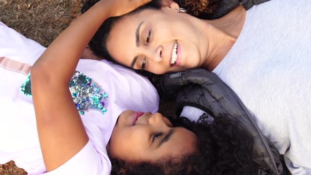 Daughter and Mother Lying Down Enjoying the Day at Park