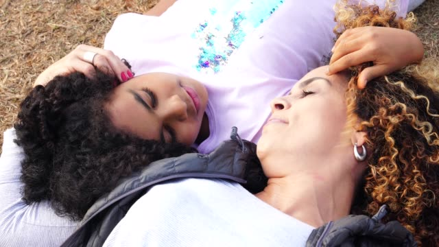 daughter and mother lying down enjoying the day at park - 40 44 years stock videos & royalty-free footage