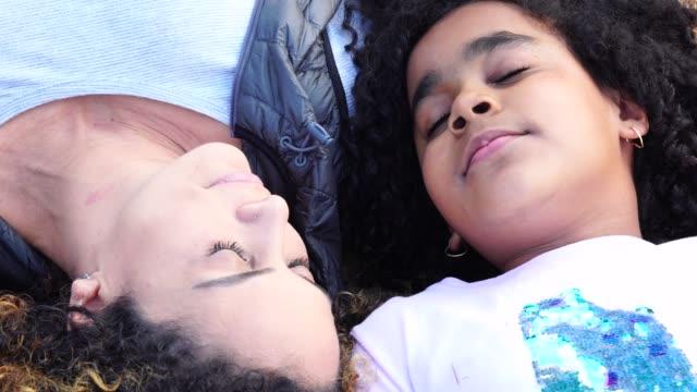 vídeos de stock, filmes e b-roll de filha e mãe deitada olhando para o céu - cabelo encaracolado