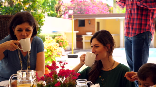 ms daughter and mother toasting with coffee mugs during family brunch - brunch stock videos & royalty-free footage