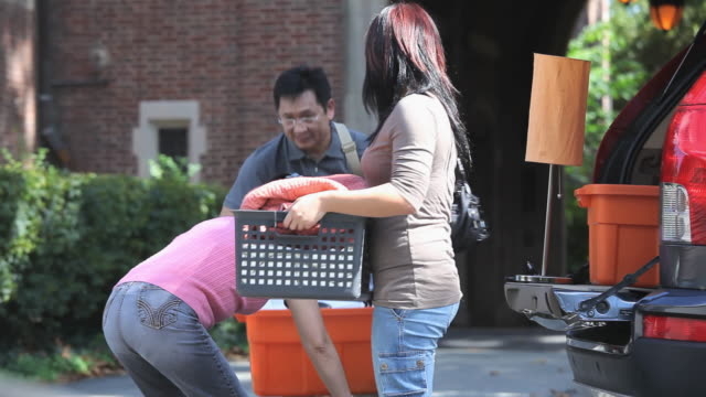 ms tu daughter and parents carrying luggage and moving towards college dorm / richmond, virginia, usa - 荷物点の映像素材/bロール