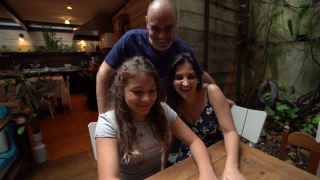 vídeos de stock, filmes e b-roll de filha e os pais usando laptop juntos - latino americano