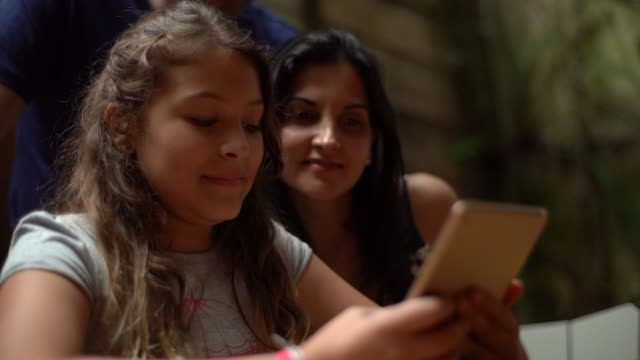 vídeos de stock e filmes b-roll de daughter and parents using mobile together - latino americano
