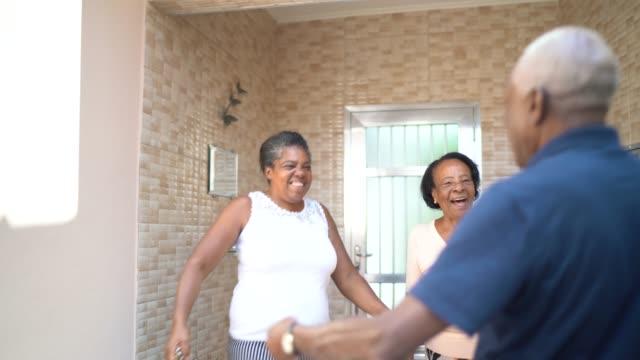 vídeos de stock, filmes e b-roll de filha chegando e pais dando um abraço em casa - 50 54 anos