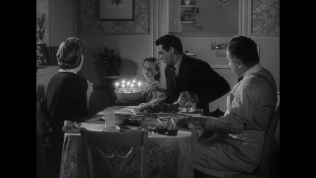 1941 daughter brings in birthday cake singing happy birthday to mother (irene dunne) with father (cary grant), and friend (edgar buchanan) - singen stock-videos und b-roll-filmmaterial