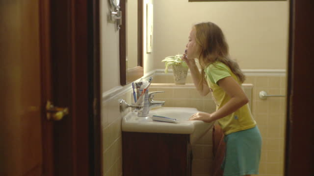 ms daughter (10-11) brushing teeth and mother getting ready in bathroom / havana, cuba - zapfen stock-videos und b-roll-filmmaterial