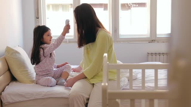 stockvideo's en b-roll-footage met dochter die de lichaamstemperatuur van de moeder met infrarode thermometer controleert - dubbel bed