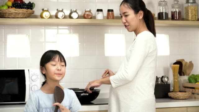 妊娠中の母親が台所で料理をしながら歌を歌って踊ったりの娘 - 歌う点の映像素材/bロール