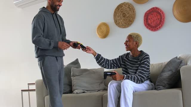お父さんとゲームをするジョイスティックを提供する娘 - dia点の映像素材/bロール