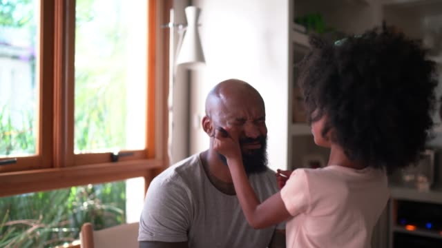 daughter doing makeup to shy father at home - candid stock videos & royalty-free footage