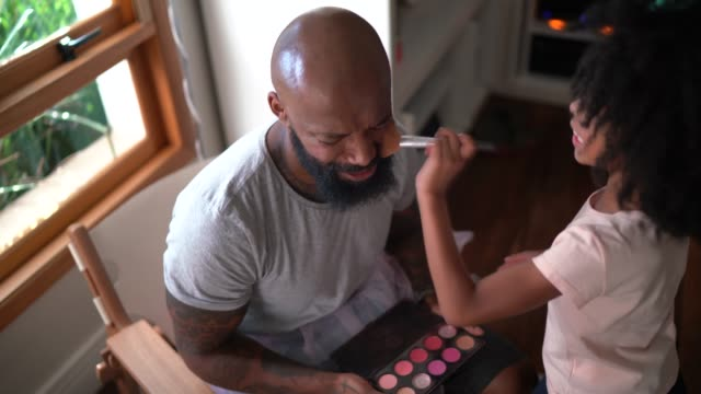 daughter doing makeup to shy father at home - playful stock videos & royalty-free footage