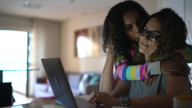 stockvideo's en b-roll-footage met dochter die moeder omhelst en kust terwijl zij thuis werkt - multitasken