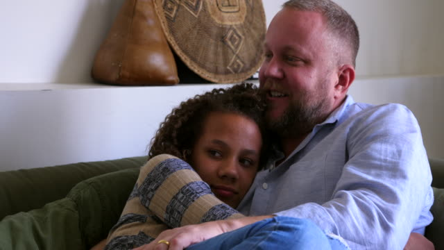 ms pan daughter embracing mother and father on couch in living room - 45 49 years stock videos & royalty-free footage