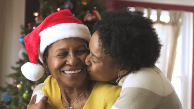 ms daughter embracing mother with christmas tree  in background / newark, new jersey, usa - kissing stock videos & royalty-free footage