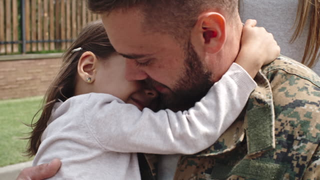 daughter embracing soldier in wheelchair - ホームカミング点の映像素材/bロール