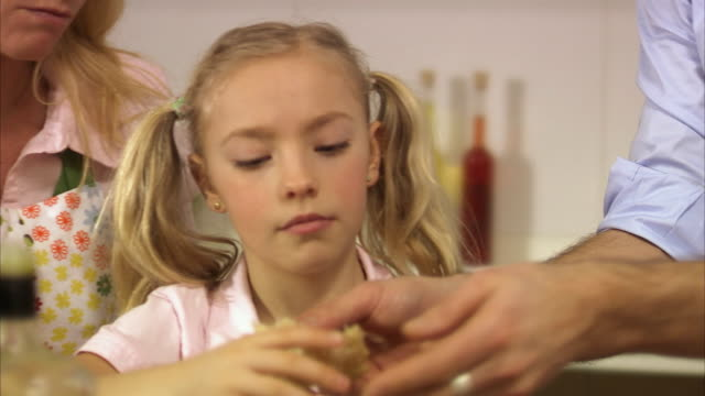 daughter gets a sandwich and eat it in the kitchen stockholm sweden. - schweden stock-videos und b-roll-filmmaterial