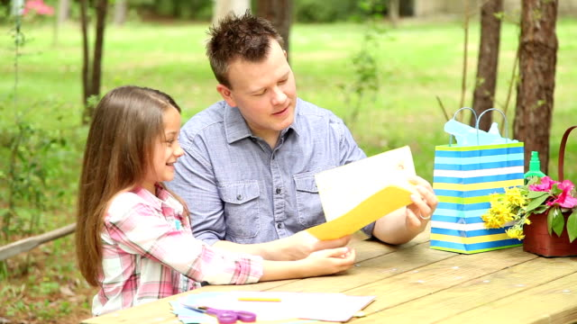 daughter gives dad handmade father's day card. outdoors. child, parent. - father's day stock videos & royalty-free footage