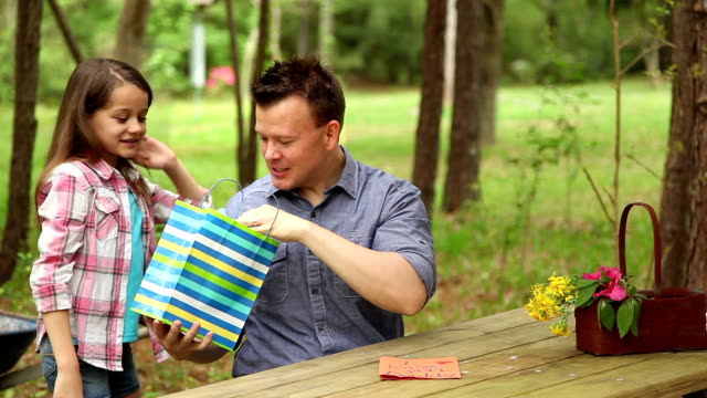 daughter gives daddy father's day gift. outdoors. child, parent. - fathers day stock videos & royalty-free footage