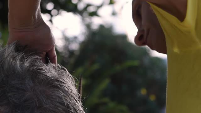 高齢者の両親に散髪を与える娘。 - 依存点の映像素材/bロール