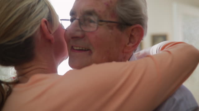 Daughter Giving Her Elderly Father A Hug