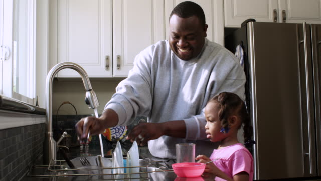 MS Daughter helping Dad to wash in kitchen sink / Dallas, Texas, USA