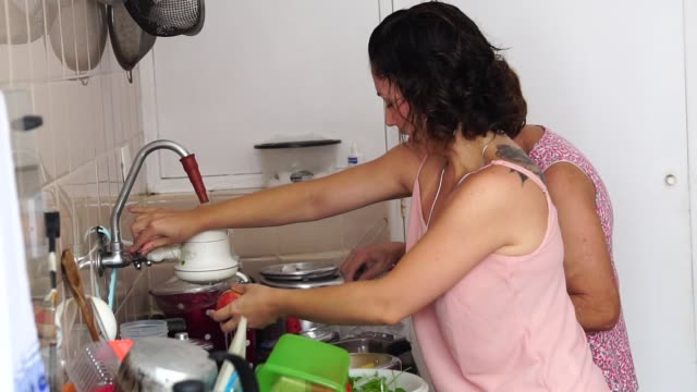 daughter helping her mother washing dish in kitchen - vassoio video stock e b–roll
