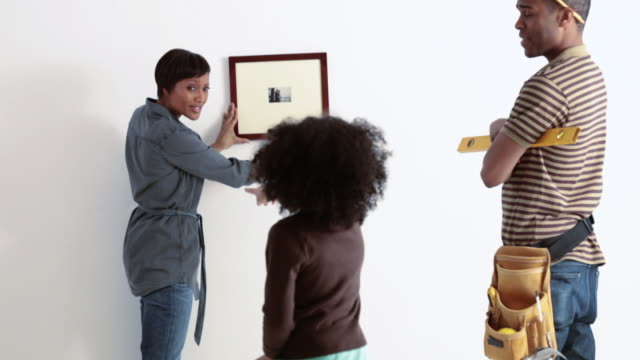 Daughter helping parents hang picture