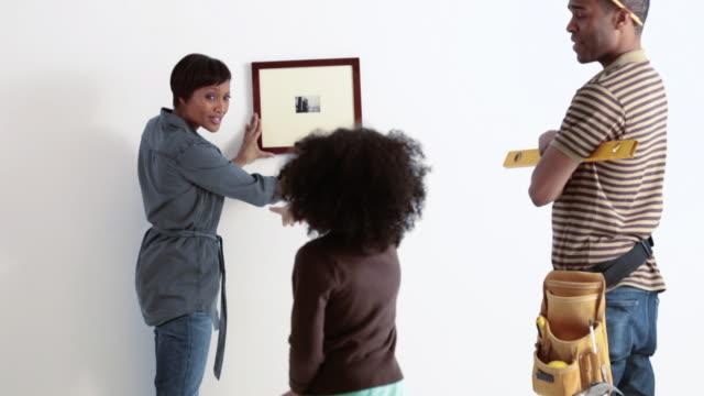 vídeos y material grabado en eventos de stock de daughter helping parents hang picture - marco
