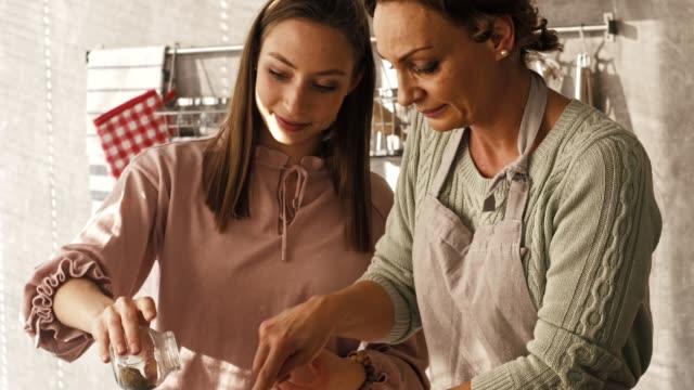 vídeos y material grabado en eventos de stock de hija ayuda a su madre cocinando - daughter