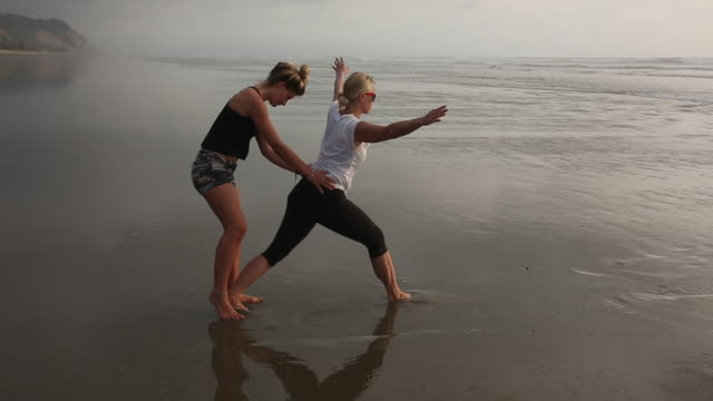 Daughter helps mother with yoga moves on beach, surf behind