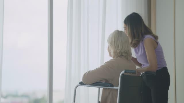 リビングルームのカートに座るための法律で母親を保持している娘。保護するウイルスcovid-19のためのマスクを着用してください。ミックススキンファミリー。 - 義母点の映像素材/bロール