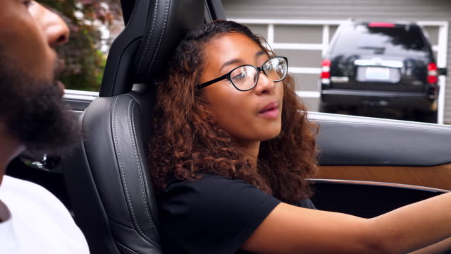 MS Daughter in drivers seat of car listening to father during driving lesson
