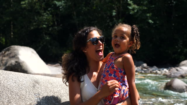 ms daughter kissing mother while hanging out by river on summer afternoon - daughter stock videos & royalty-free footage