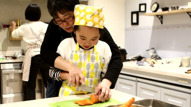 daughter learning how to cut carrots from mother - 集中点の映像素材/bロール