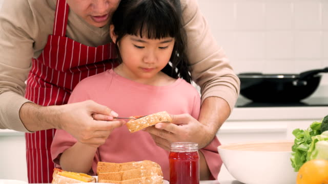 daughter learning how to make toast from father that putting strawberry jam on bread sheet - strawberry jam stock videos & royalty-free footage